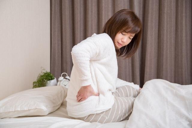 起きるのも辛いほどの腰痛に悩む女性